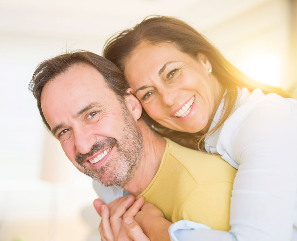 A happy couple hugging and smiling at Aesthetic Periodontal & Implant Specialists