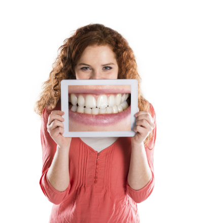 Red head woman holding up picture of teeth